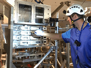 A CERN technician installs one of the sample arrays shipped from PNNL.