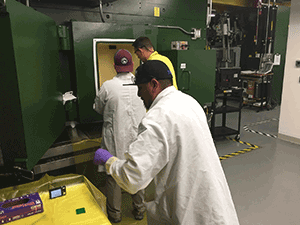 RPL technicians measure dose rates and contamination levels before taking samples out of a hot cell.